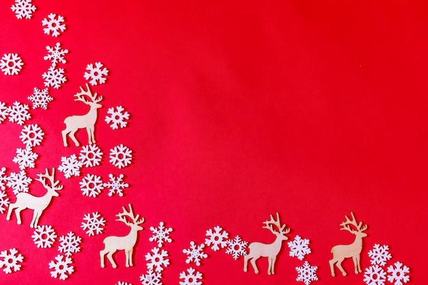 Cerf blanc décoratif et flocons de neige blancs décoratifs sur fond rouge. noël à plat