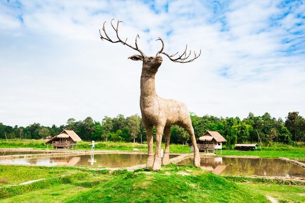 Cerf en bois géant dans la rizière