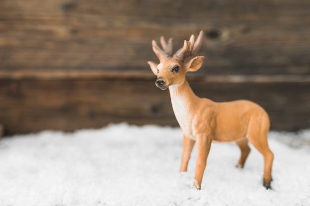 Cerf jouet sur la neige près du mur en bois