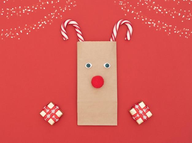Cerf de noël fait de sac à provisions et de deux cannes de noël avec des coffrets cadeaux sur fond rouge