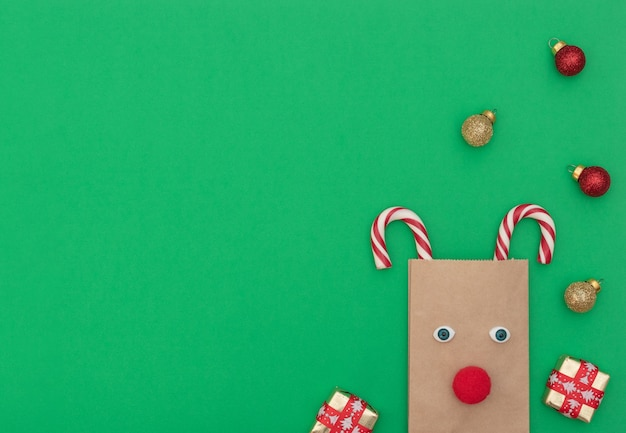 Cerf de noël en sac à provisions artisanal et deux cannes de noël avec coffrets cadeaux et boules de noël sur fond vert