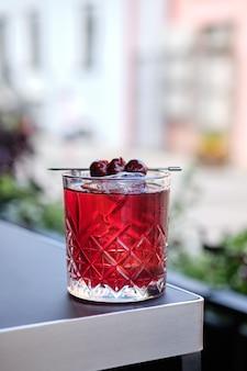 Cerise cocktail sur le bord de la table sur la terrasse extérieure (photo avec une faible profondeur de champ)