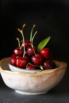 Cerise fraîche mûre avec des feuilles dans un bol en argile sombre.