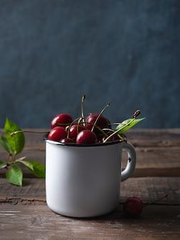Cerise fraîche en tasse sur la vieille table en bois