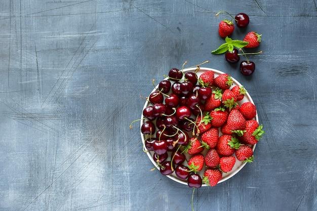 Cerise et fraise sur une assiette blanche. aliments sains, vitamines. déjeuner d'été