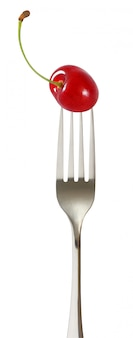 Cerise rouge avec une tige empalée sur une fourche isolée.