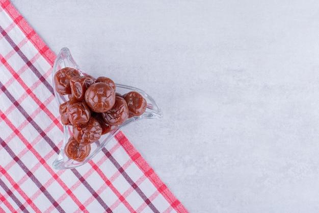 Cerises aigres brunes à moitié séchées dans une tasse sur fond de béton. photo de haute qualité