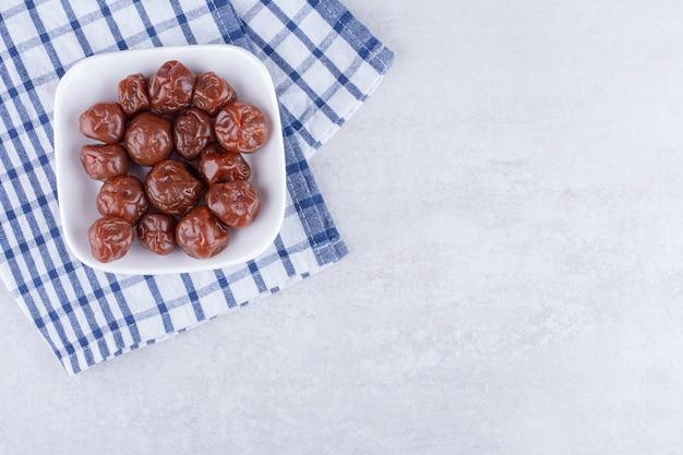 Cerises aigres brunes à moitié séchées dans une tasse sur une surface en béton