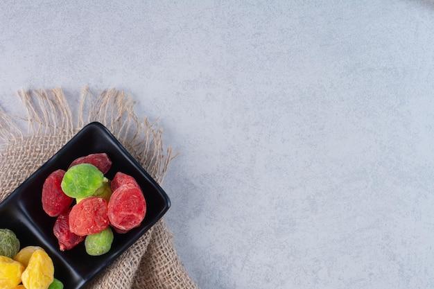 Cerises et baies multicolores séchées sur fond de béton.