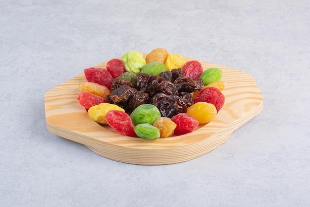 Cerises et baies multicolores séchées sur une surface en béton.