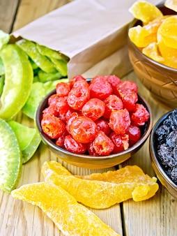 Cerises confites, melons, raisins secs dans des bols, pomelo confits dans un sac en papier sur fond de planches de bois