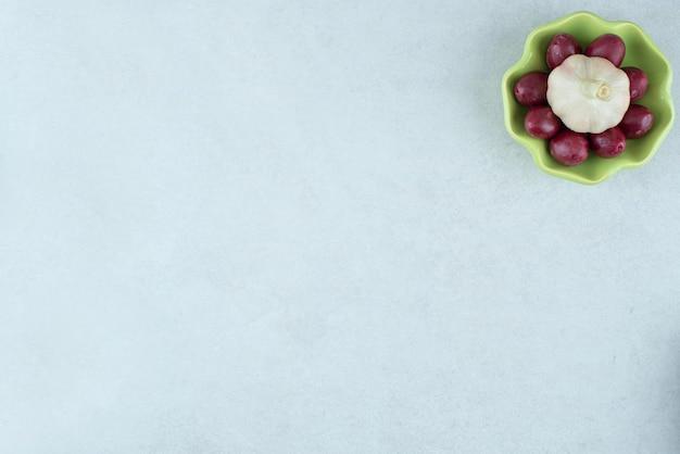 Cerises de cornouiller marinées dans un bol avec de l'ail frais.