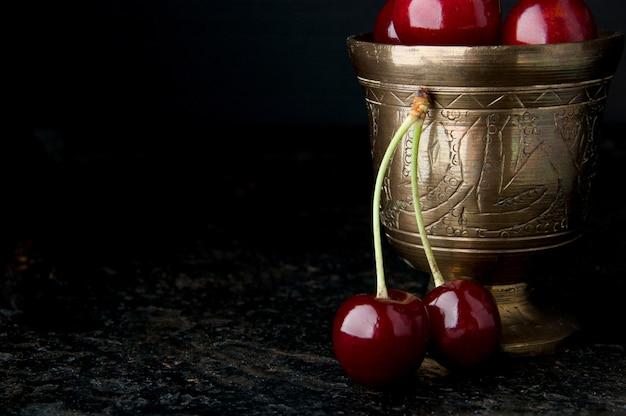 Cerises dans un bol en bronze sur fond noir