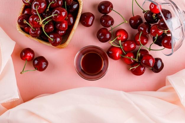 Cerises dans un vase et une assiette avec un verre de thé vue de dessus sur une surface rose et textile