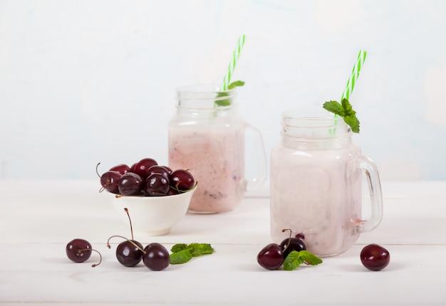 Cerises douces et smoothies au lait dans deux bocaux en verre avec une paille et des cerises douces dans une tasse