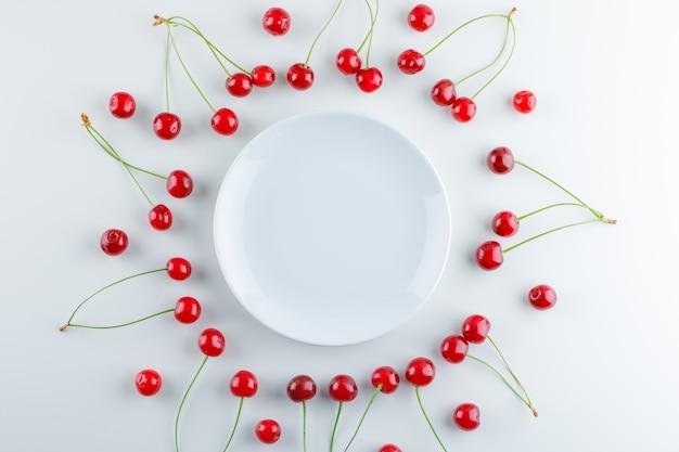 Cerises éparses avec assiette vide, pose à plat.
