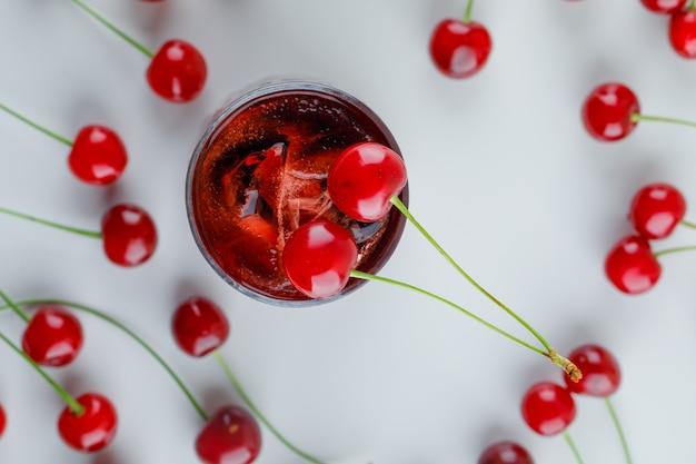 Cerises éparses avec boisson glacée, pose à plat.