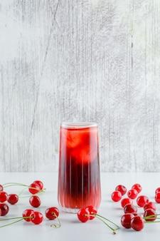 Cerises éparses avec vue de côté de boisson glacée sur table blanche et grungy