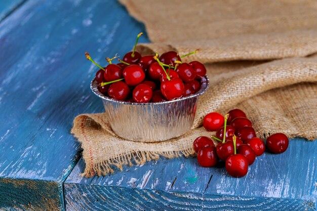 Cerises fraîches dans une vieille tasse en métal. mug métal cerises fraîches sur une vieille table en bois.