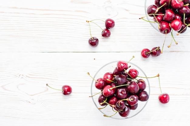 Des cerises fraîches mûres dans de l'eau tombe dans des bols sur une table en bois blanche