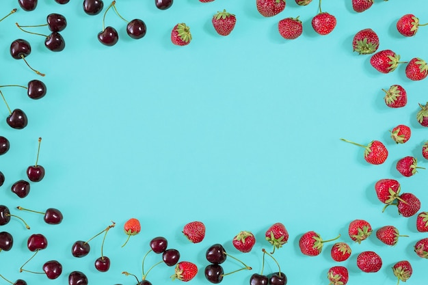 Cerises et fraises fraîches sur la vue de dessus de fond de menthe