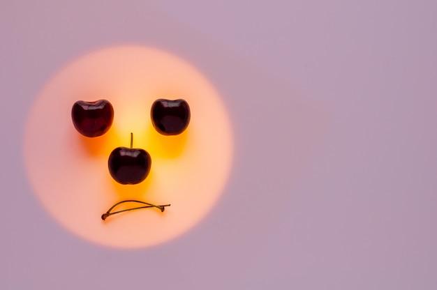 Cerises fruits mis sur la lumière de couleur orange définie comme visage ennuyeux.