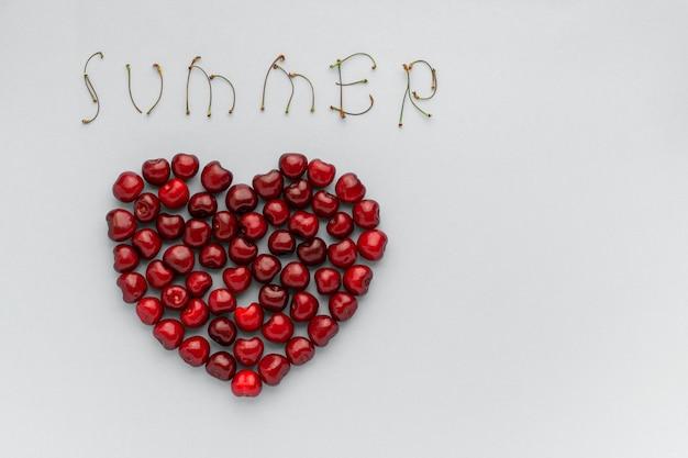 Cerises de fruits rouges en forme de coeur et de texte ete