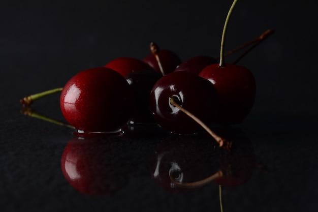 Cerises, avec des gouttes d'eau sur fond noir avec reflet
