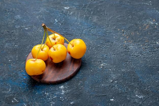 Cerises jaunes fraîches fruits mûrs et sucrés isolés sur des baies de fruits sombres, fraîches moelleuses