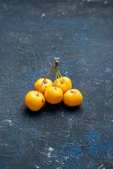 Cerises jaunes fraîches isolées sur un bureau sombre, baies de fruits frais moelleux juteux