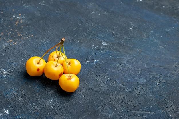Cerises jaunes fraîches isolées sur un bureau sombre, baies de fruits frais moelleux