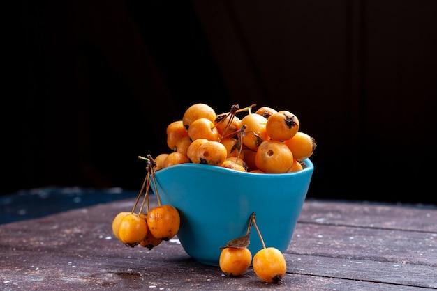 Cerises jaunes moelleuses fraîches et mûres à l'intérieur d'un bol bleu sur brown