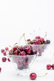 Les cerises mûres fraîches dans l'eau tombe dans des bols sur une table en bois blanche. espace de copie