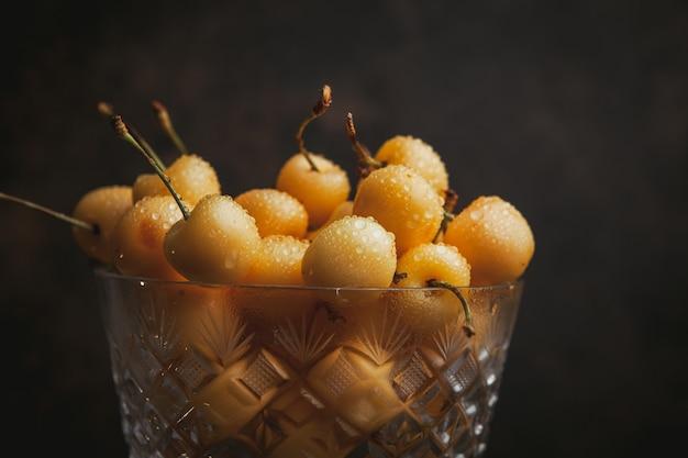 Cerises plus pluvieuses dans un grand bol de fruits sur un brun foncé. fermer.