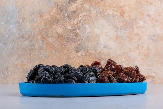 Cerises et prunes séchées dans un plateau bleu.