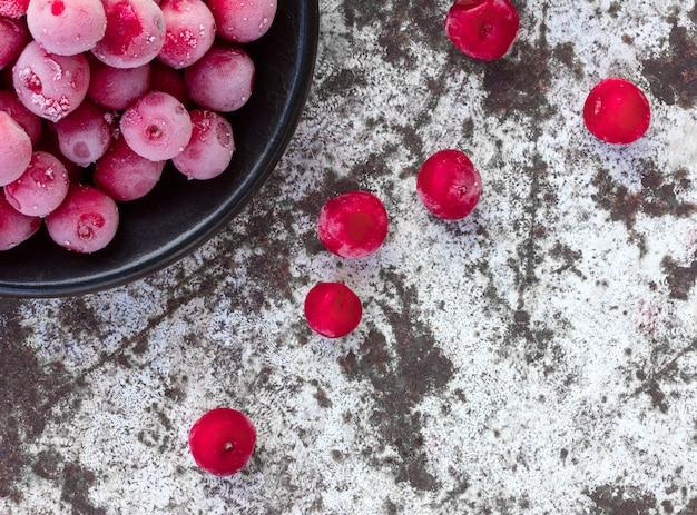 Cerises rouges congelées sur la surface blanche du vieux minable.