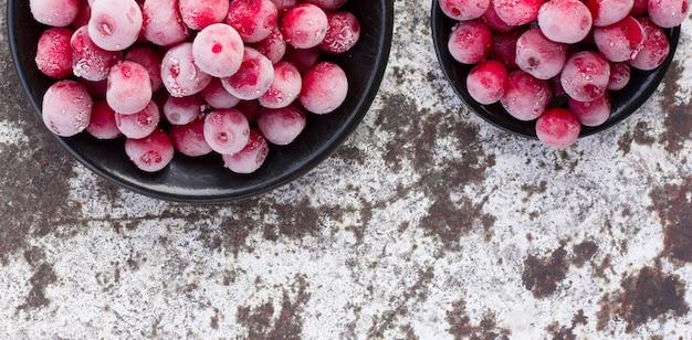 Cerises rouges congelées sur une surface métallique dénudée blanche