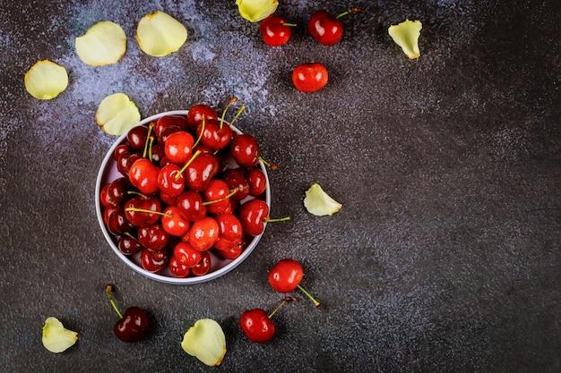Cerises rouges dans une assiette sur une surface sombre