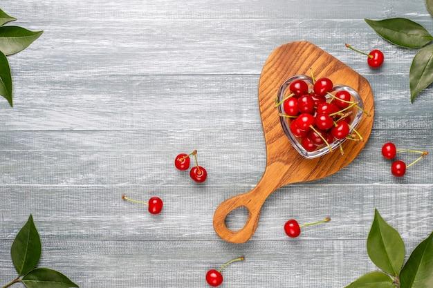 Cerises rouges dans un bol sur une table grise
