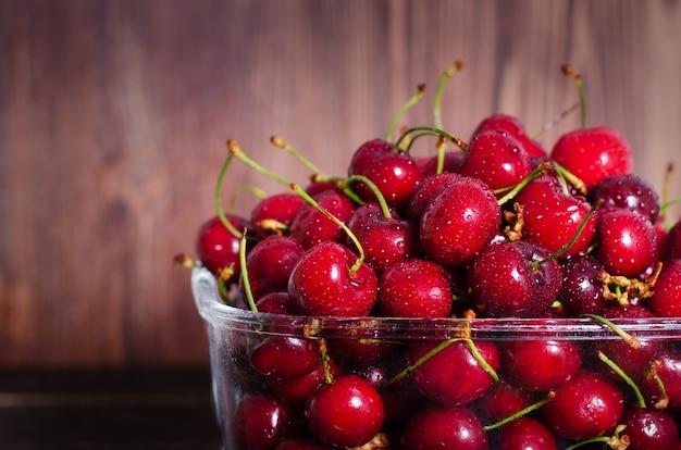 Cerises rouges douces dans un bol en verre. concept d'été et de récolte. végétalien, végétarien, nourriture crue