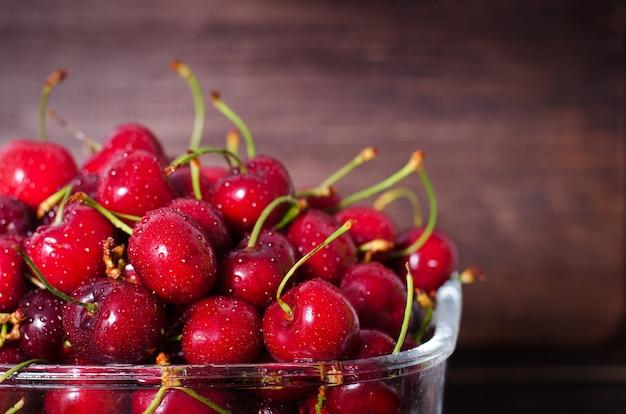 Cerises rouges douces dans un bol en verre sur un fond en bois foncé. concept d'été et de récolte. végétalien, végétarien, nourriture crue