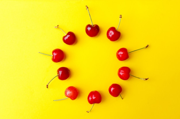 Cerises rouges fraîches sur fond jaune, publicité, affiche.