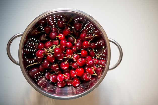 Cerises rouges fraîches à laver dans une passoire.