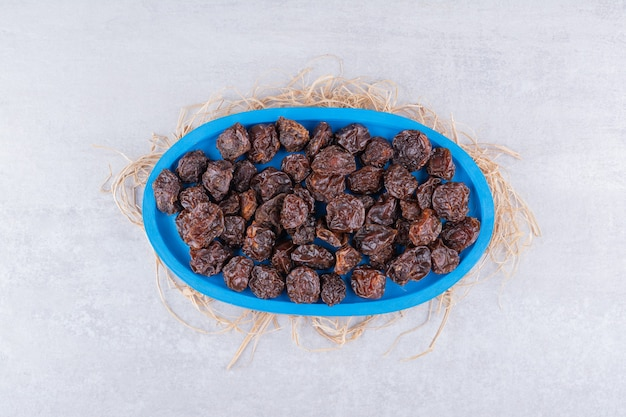 Cerises séchées brunes à l'intérieur d'un plat sur une surface en béton
