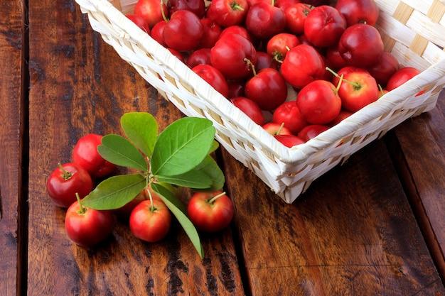 Cerisier d'acérola brut, frais, boîte sur une table en bois rustique, fruits antioxydants