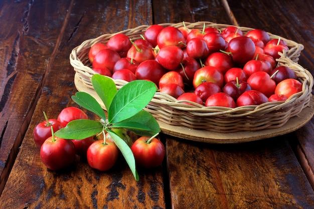 Cerisier acérola brut, frais, dans un panier en forme de coeur sur une table en bois rustique