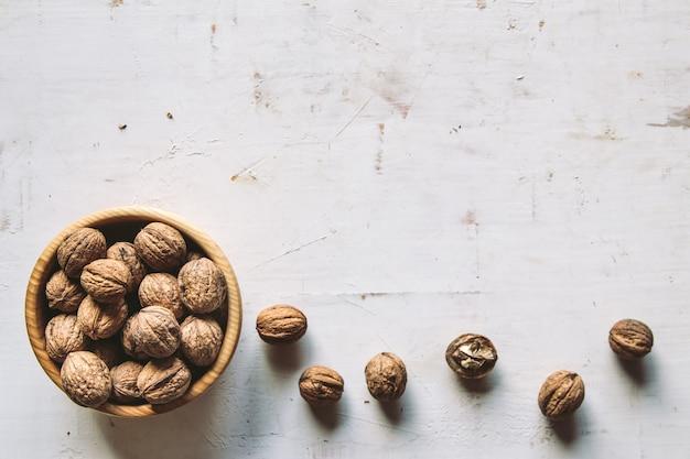 Cerneaux de noix dans un bol en bois et noix entières sur une table