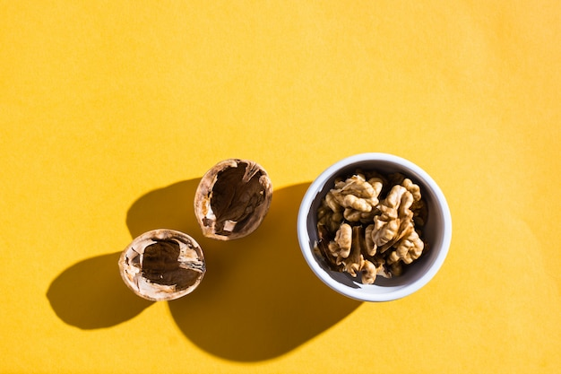 Cerneaux de noix dans un bol et coquilles de noix sur une table jaune