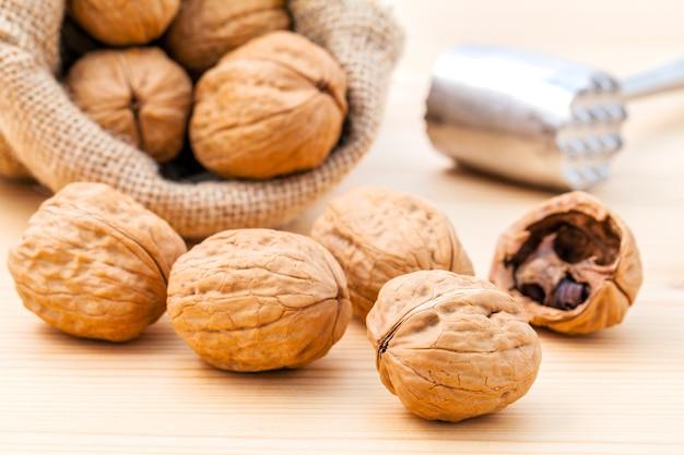 Cerneaux de noix et noix entières sur fond de bois.
