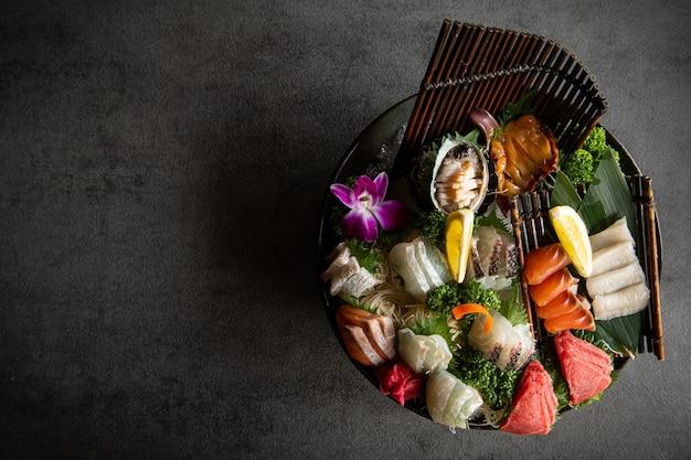 Un certain nombre de sashimi frais sont placés sur une assiette des baguettes et de la sauce soja sont placés